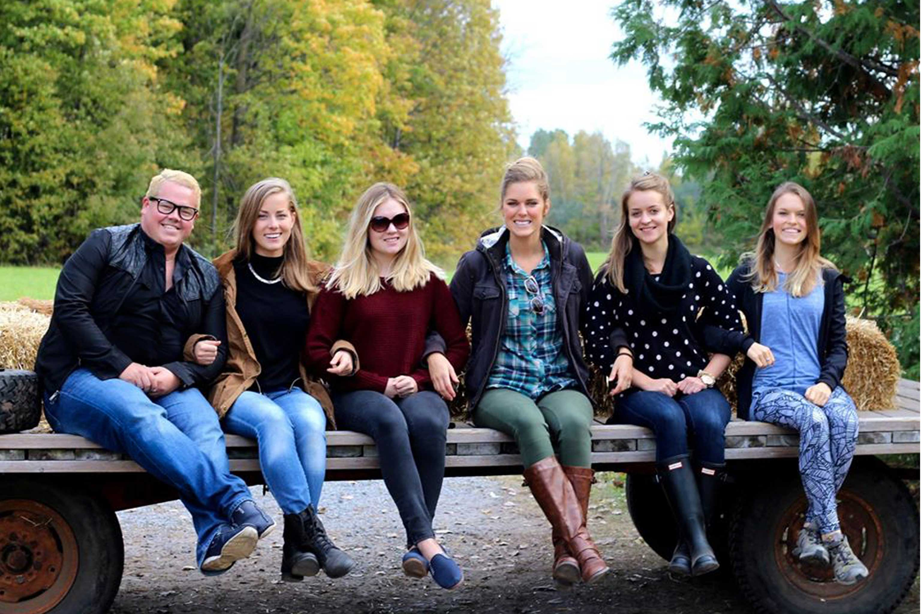 A group of 6 smiling people sitting on a flat trailer behind a truck, with fall foliage in the background