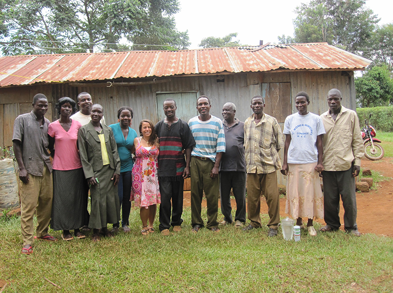 An IHN representative posing with a group of locals outside a metal roofed structure
