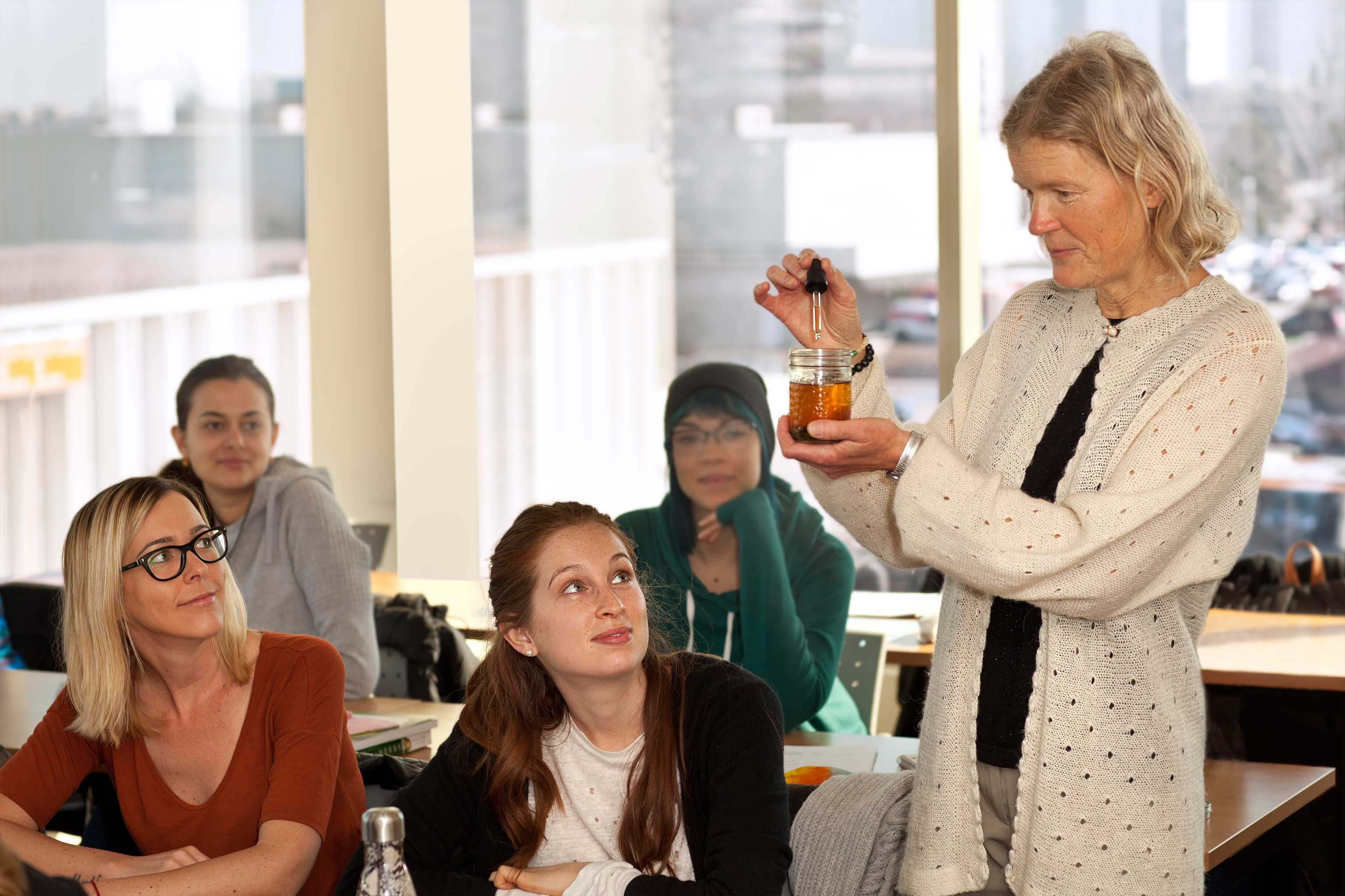 An IHN instructor holding a jar of liquid and an eyedropper teaches students in a classroom.